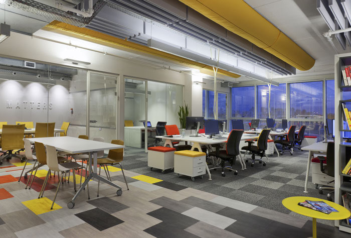 תכנון חלל צבעוני עם תקרה חשופה ושטיח צבעוני למשרד הייטק