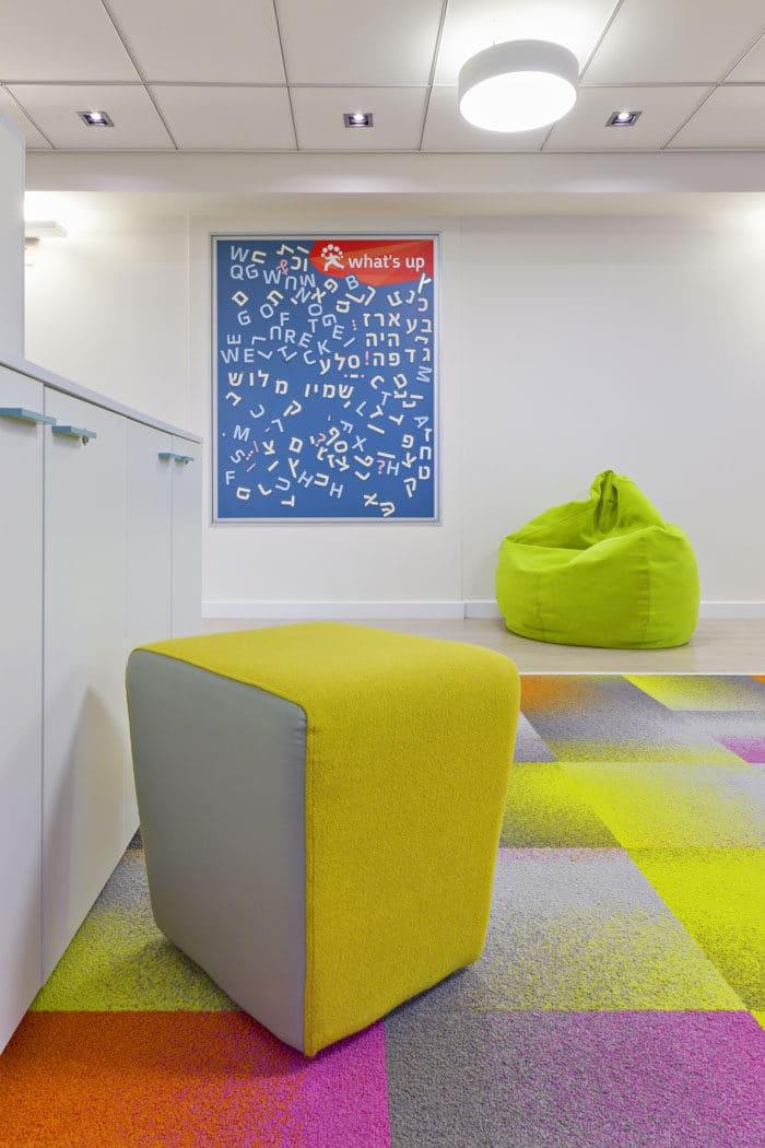 איזור עבודה עם כורסאות צבעוניות ומשחקי קיר משלימים ליצירת סביבה עבודה נוחה ומהנה