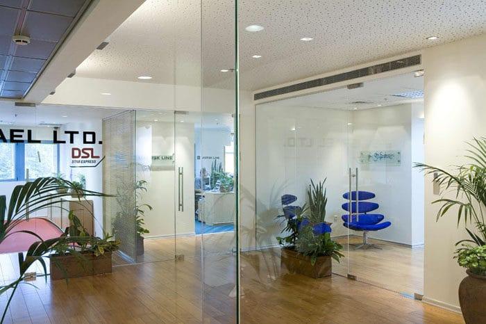 קירות זכוכית מרצפה עד תקרה בשילוב רצפת פרקט וצמחיה