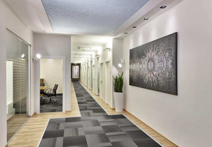 עיצוב מסדרון מוליך של רצפת אריחים בגווני אפור משולבים עם פרקט במשרדים לחברת טקסטיל