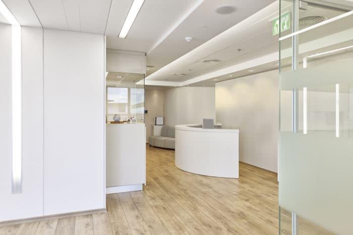 עיצוב מסדרון במשרדים הכולל מבטח על קירות זכוכית,עמדות תצוגה ופסי תאורה שקועים