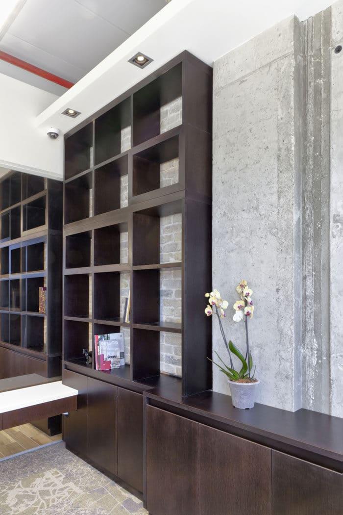 עיצוב קיר ספריה מעץ על רקע קיר בלוקים