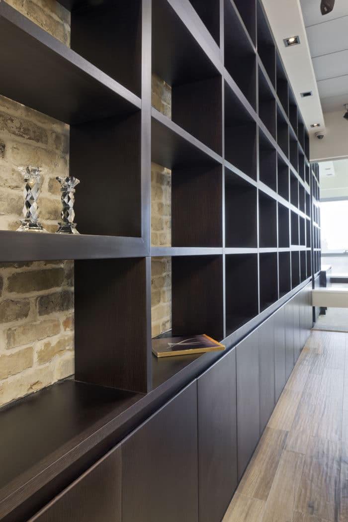 קיר ספריה מרצפה עד תקרה במשרד באווירה ביתית ויוקרתית