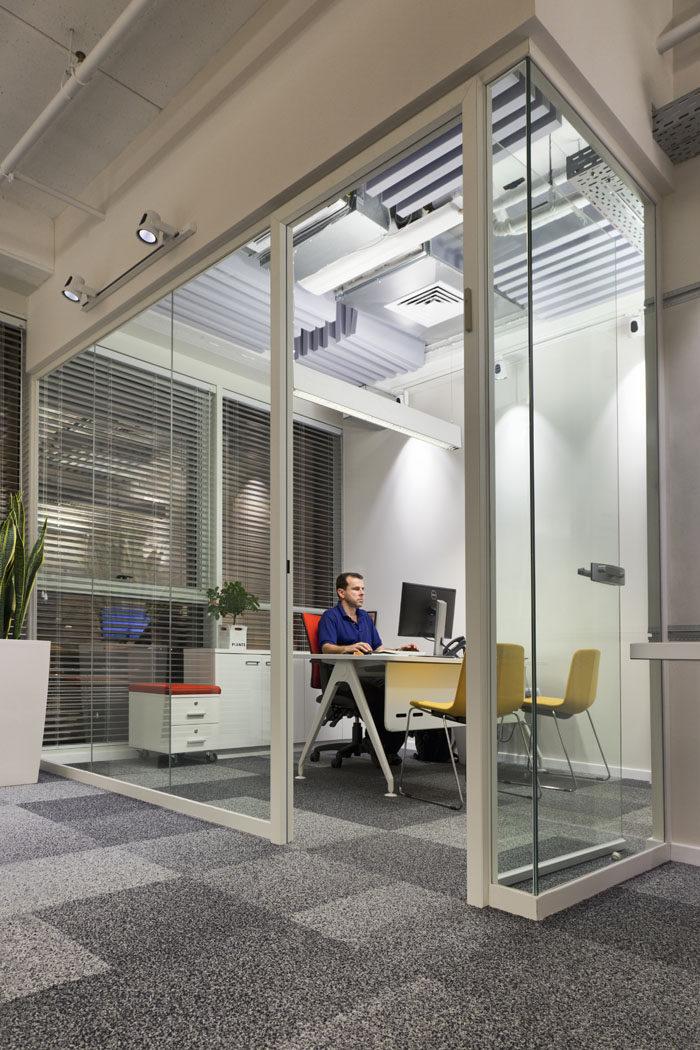 עיצוב חדר מנהל מזכוכית עם צבעוניות לפי צבעי הלוגו של החברה.