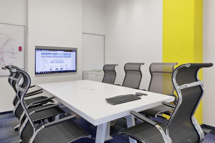 חדר ישיבות מזכוכית עם קיר מחיק מלוח אמייל ועמוד צהוב