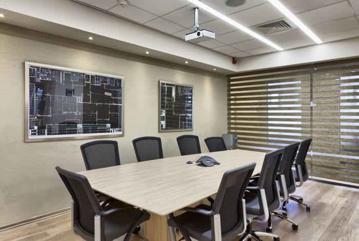 חדר ישיבות מעץ עם כסאות שחורים ותמונות של שרטוטים אדריכליים כקישוט