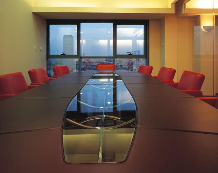 עיצוב חדר ישיבות עם שולחן מעור וזכוכית וכיסאות ער אדומים