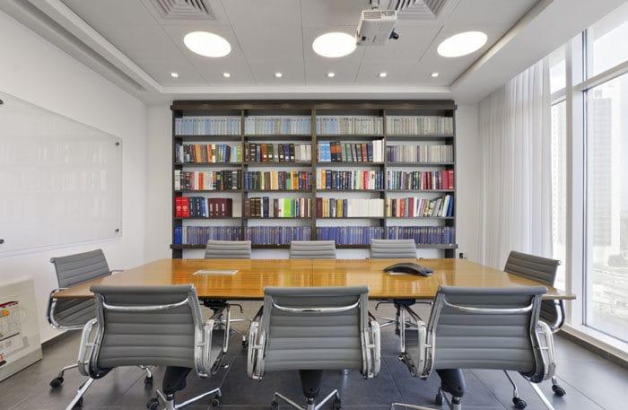 חדר ישיבות משרד עורך דין עם ספריה ולוח זכוכית מחיק