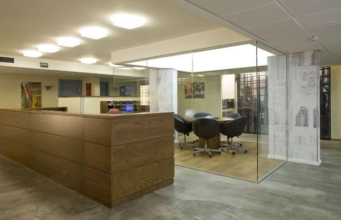 מבט כולל של דלפק קבלה מעץ, חדר ישיבות שקוף ואריחי ריצוף דמוי בטון