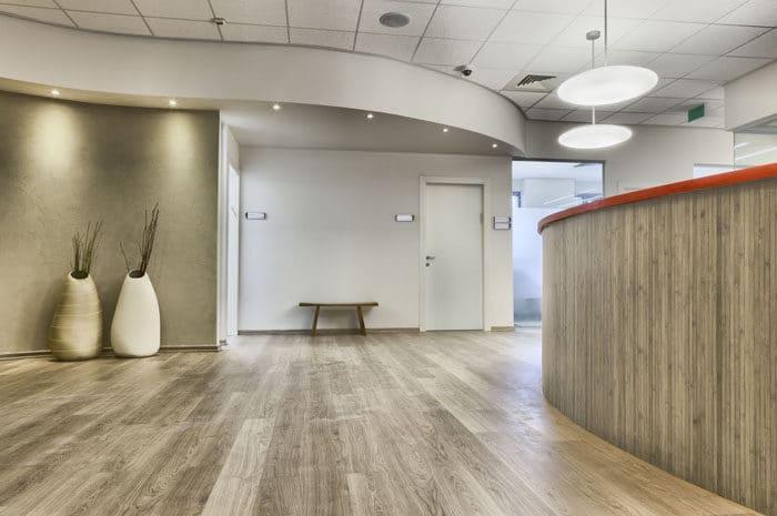 כניסה למשרדי חברת תקשורת בינלאומית מעוצבים באווירה אינטימית בגווני עץ ובז'