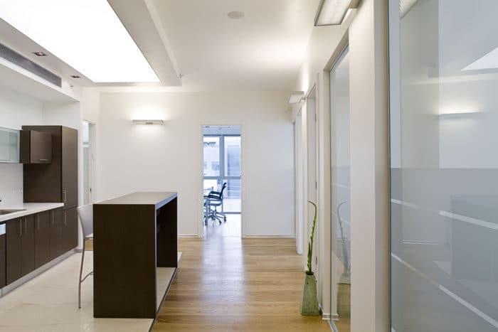 מבט על מסדרון המשרד המשלב בתוכו רבדים שונים של חומרים ואיזורים