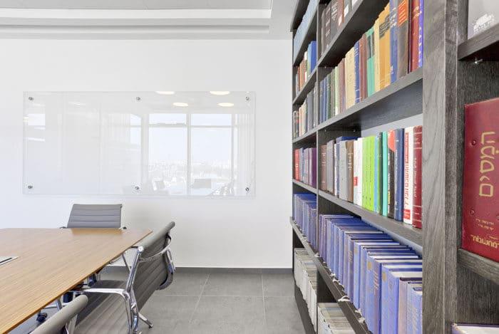 ספריה מרצפה עד תקרה ולוח מחיק מזכוכית בחדר ישיבות במשרד עורכי דין