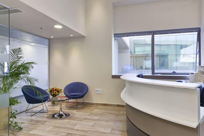עיצוב כניסה למשרדים הכולל דלפק קבלה בצבעים שונים ופינת המתנה כחולה