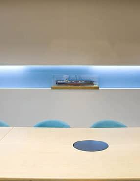 עיצוב נישות בקיר בחדר ישיבות עם מודלים של אניות