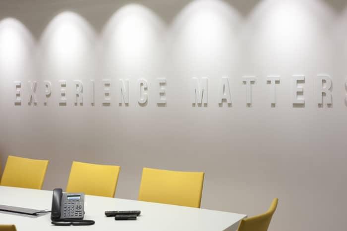 עיצוב קיר לבן עם כיתוב ותאורה מעוצבת בחדר ישיבות במשרדי חברת הייטק
