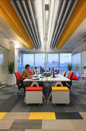 חלל פתוח צבעוני עם תקרה חשופה במשרדי חברת הייטק. עיצוב משרדים צבעוני, מהנה ומיוחד