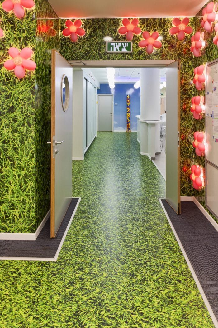 עיצוב מבואה בעזרת מוטיב של דשא ירוק המתבטא בעיצוב רצפה ירוקה וקירות ייחודים