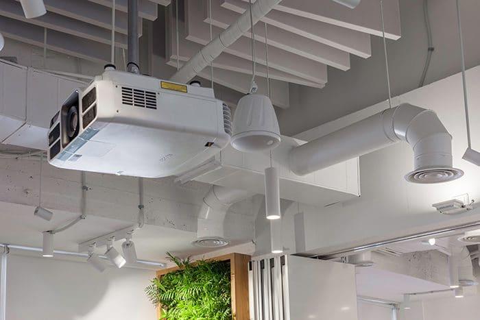 עיצוב תקרה חשופה בלבן עם מקרן תלוי וספוגים אקוסטיים