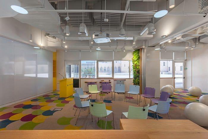 מרכז חדשנות עם כיסאות צבעוניים ותקרה לבנה חשופה