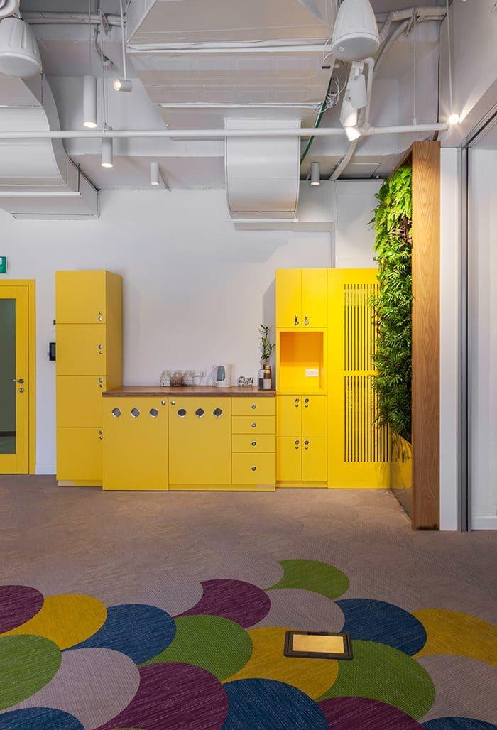 מטבחון צהוב עם רצפה צבעונית וקיר ירוק