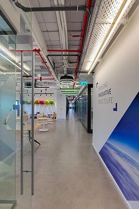 עיצוב כניסה למשרדי הייטק עם תקרה חשופה ופופים צבעוניים