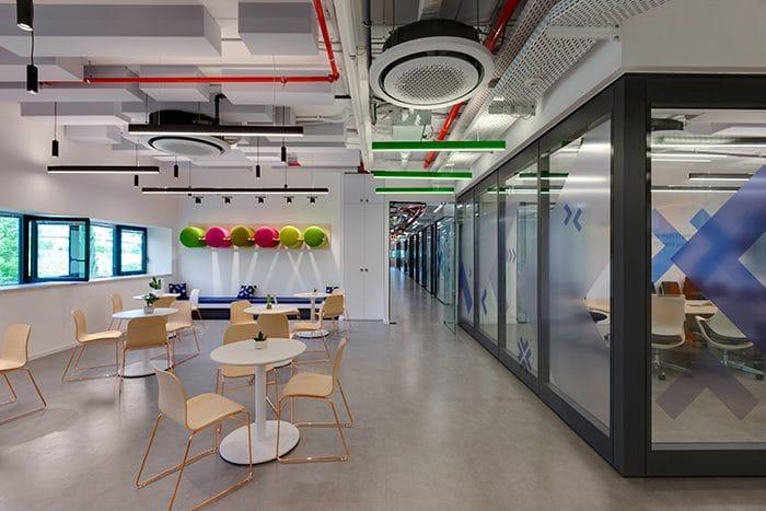 עיצוב תקרה חשופה למשרדים עם מערכות גלויות וגופי תאורה תלויים