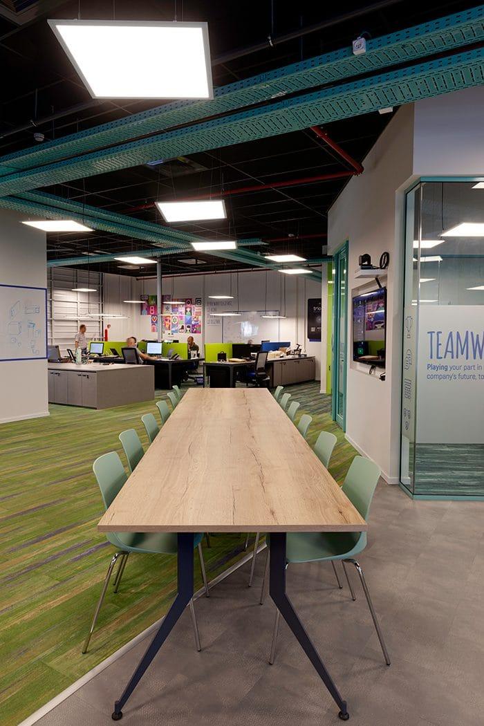 עיצוב כניסה למשרדים עם תקרה שחורה, מערכות גלויות ומנורות תלויות
