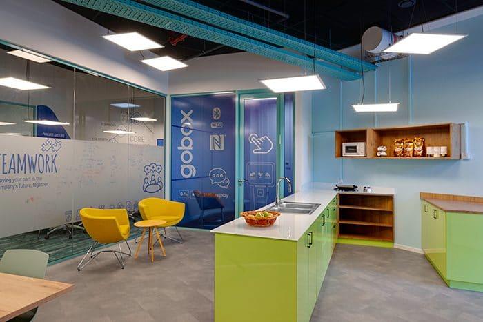עיצוב קפטריה, פינת ישיבה ותא טלפון לחברת הייטק עם קירות צבעוניים ותעלות חשמל גלויות