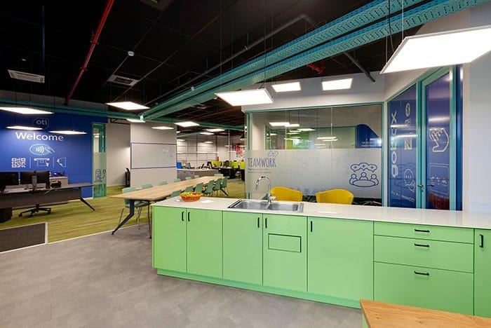 עיצוב חלל כניסה למשרדי חברת הייטק עם מטבחון ירוק ותקרה שחורה