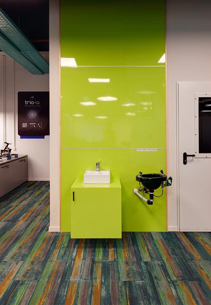 עיצוב פינת עבודה עם ברז חירום וקיר מבריק בגוון ירוק תפוח