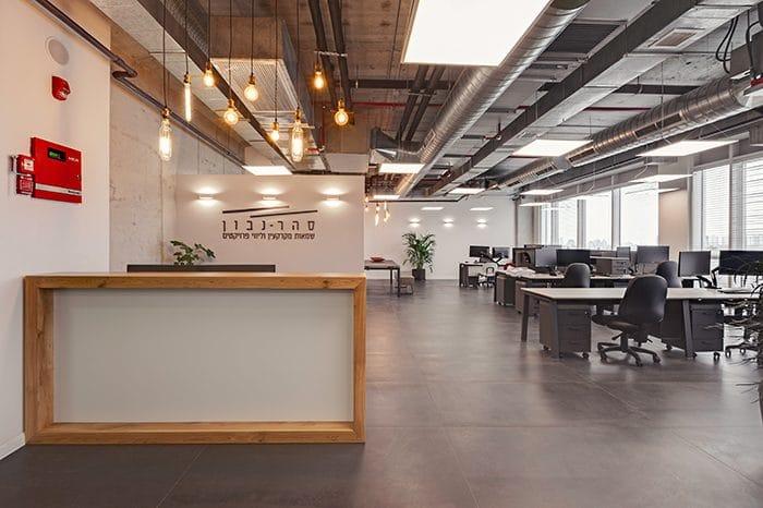 עיצוב תקרה חשופה למשרדים עם גופי תאורה תלויים